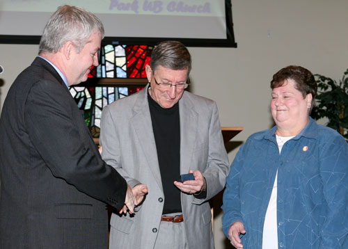 Bishop Phil Whipple (left) presents a retirement pin to Larry Taylor, as Larry's wife Linda looks on.