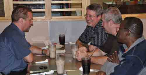 Jeff Bleijerveld (right) at Pizza hut talking to three bishop: Brian Magnus (Canada), Phil Whipple (USA) and Billy Simbo (Sierra Leone).