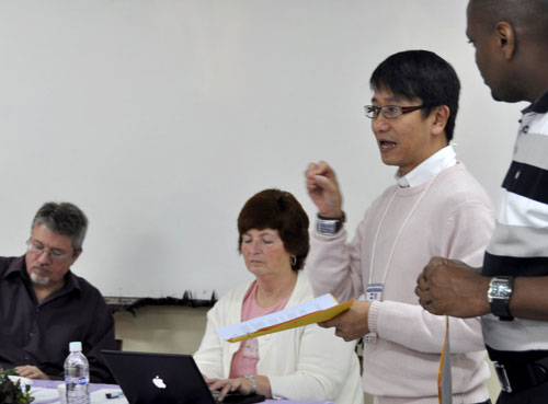 Ajiax Wo gives his report as superintendent of Hong Kong Conference. L-r: Brian Magnus (chair), Donna Hollopeter (secretary), Ajiax, and Orville Brown (translator).
