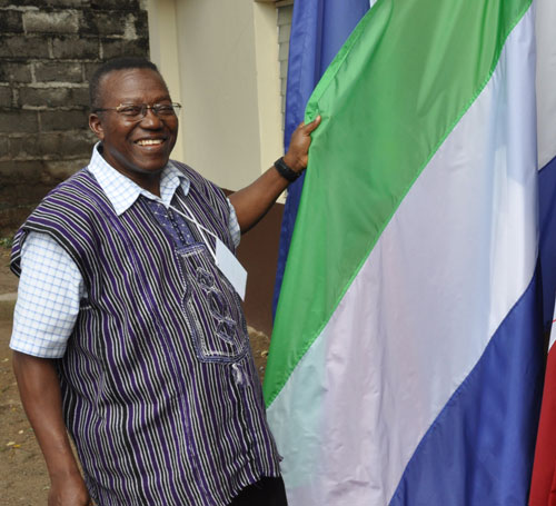 Billy Simbo, Bishop of Sierra Leone Conference, beside the Sierra Leonean flag.