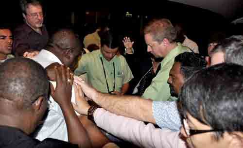 General Conference delegates lay hands in prayer on Oliam Richard, Superintendent of Haiti.
