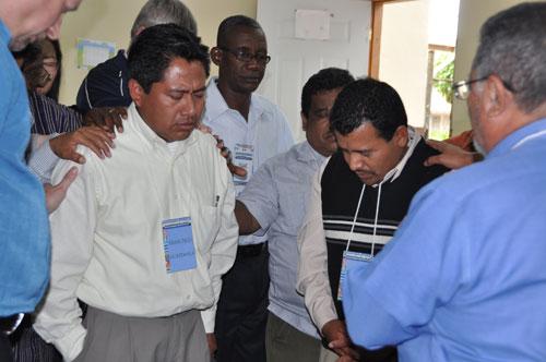 The General Conference delegates pray over Francisco Najera (left) and Rolando Valenzuela of Guatemala Conference.