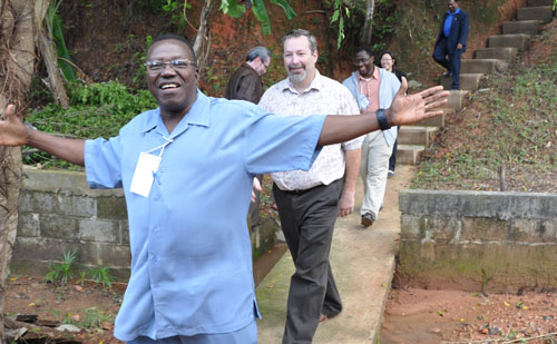 Billy Simbo, bishop of Sierra Leone Conference, leads the way down from the hill overlooking the camp. Jeff Dice is directly behind him.