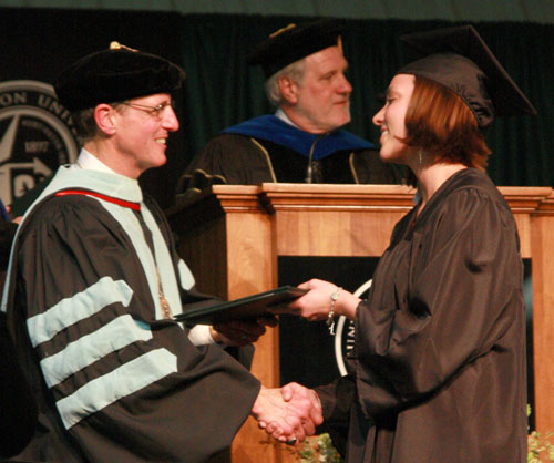 Dr. G. Blair Dowden presents a diploma to a student.