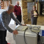 Josh Kesler rolling in a photocopier, as Phil Whipple and Cathy Reich watch.