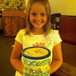 Julie with her bucket of money collected from schoolmates.