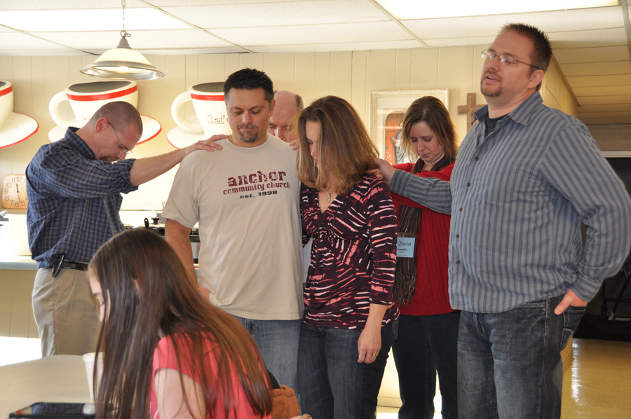Associate pastor Matt Kennedy (right) and members of the resource team pray for Tim and Tara Hallman as they prepare to begin a four-month sabbatical.