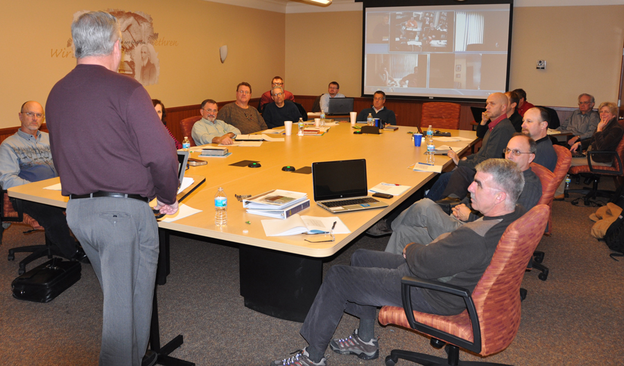 """Bishop Phil Whipple teaching the """"Leading a Governing Board"""" class. The screen in the back of the room shows persons attending remotely."""