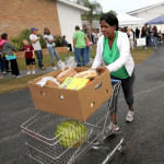 Joyce Dismuke pushes a shopping cart loaded with food from the food pantry. (Photo by Jim Tiller for the Daytona Beach News-Journal)