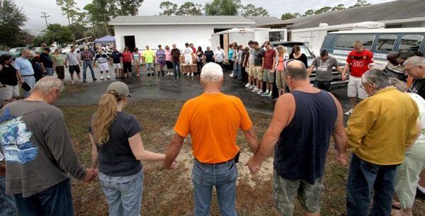 Pastor Chuck McKeown leads a group of volunteers in a quick prayer outside First UB church in Holly Hill, Fla., before serving food to the needy Tuesday morning, January 8, 2012. (Photo by Jim Tiller for the Daytona Beach News-Journal)