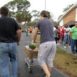 Volunteer Todd Rupp, a youth pastor at Emmanuel Community Church, helps Keith Chandler take his shopping cart of food to his car. (Photo by Jim Tiller for the Daytona Beach News-Journal)