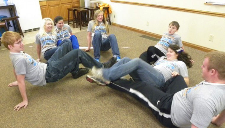 """The youth group enjoyed playing games to occupy their time. They made a soccer ball from twine, duct tape, paper bags and cloth, and then played a game of """"crab crawl"""" soccer. From left: William Holbrook, Cassie Lieser, Christy Burcham, Ambir Myers, Bo Myers, Cathy Burcham, and Derek Montgomery."""