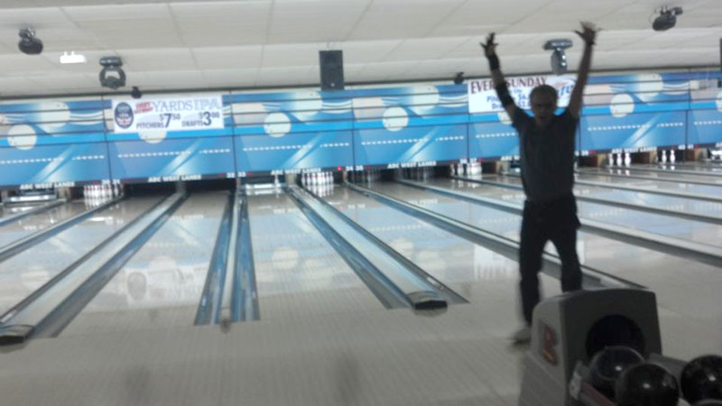 Greg Helman celebrates with the final delivery, which gave him a total of 800 points. He needed nine pins, and as you can see, only one is left standing. Greg's wife, Marty, secretly took this photo while hiding behind other team members.