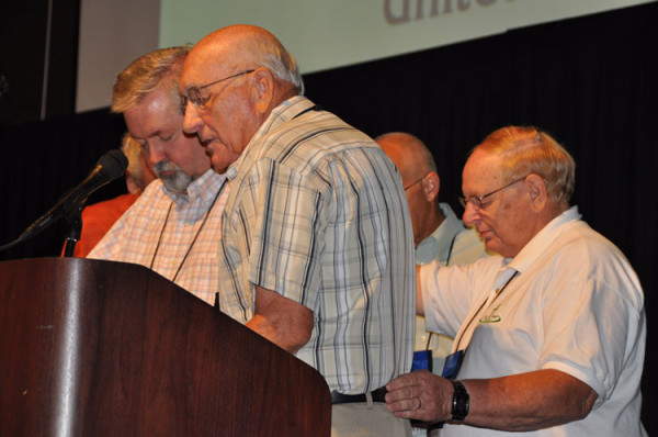 Bishop C. Ray Miller (foreground) praying for Bishop Whipple as he begins a second term.