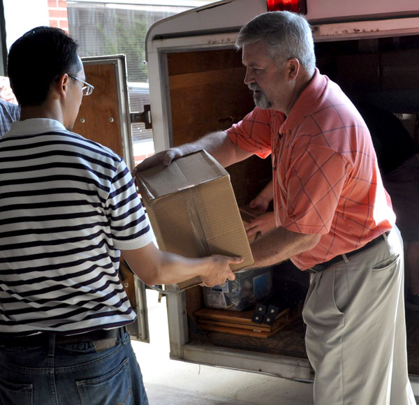 Bishop Phil Whipple (right) and Frank Y unload the Huntington University trailer.