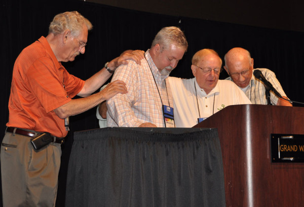 L-r: Ron Ramsey, Phil Whipple, Ray Seilhamer, and C. Ray Miller. Standing behind Bishop Whipple, mostly hidden, is Paul Hirschy. Bishop Emeritus Ray Seilhamer is praying for Bishop Whipple.