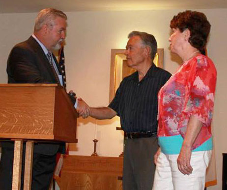 Bishop Phil Whipple (left) recognizing Dick and Darlene Case.