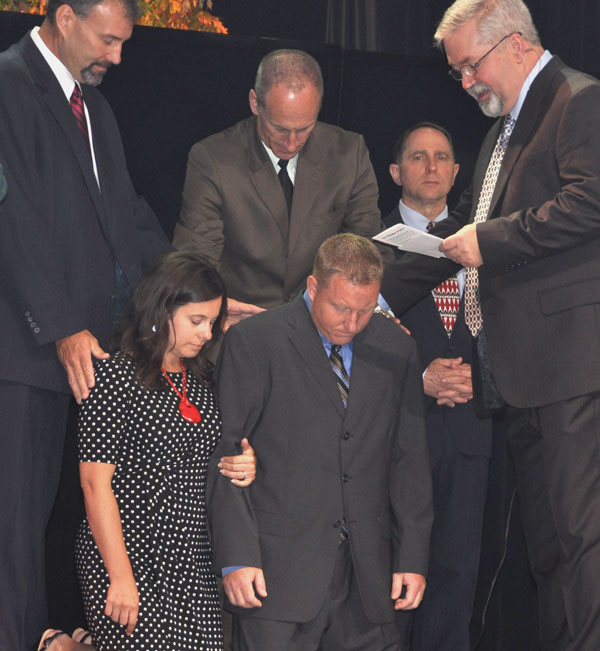 Bishop Whipple conducts the ordination of Jason Holliday (kneeling with wife Christy).