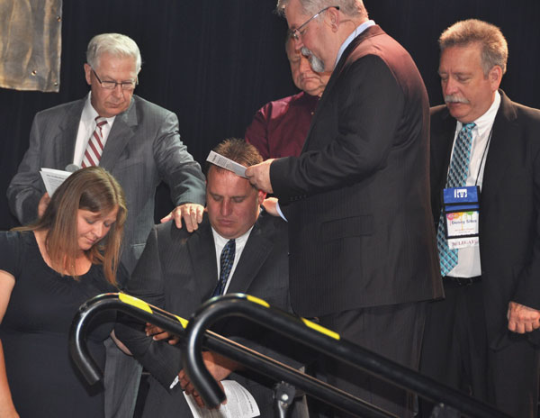 Todd and Amy Yoder kneel as Bishop Whipple conducts the ordination ceremony.