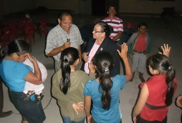 Juanita Chavez amidst a group of praying Hondurans.