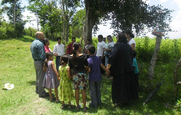 A circle of Hondurans praying in an outside location.