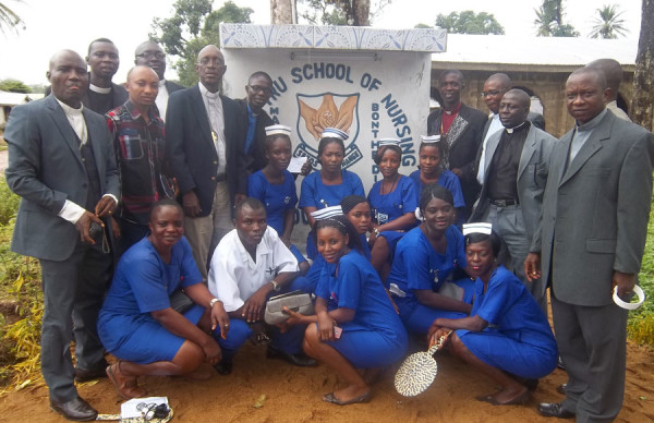 Nursing students and leaders around the school's sign at Mattru.