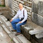 Dr. Mark Fairchild demonstrating an ancient public latrine.