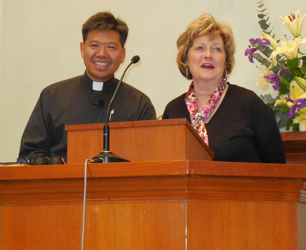 Dr. Sherilyn Emberton brings greetings to the Zion UB church in Hong Kong. Translating for her is the church's pastor, Rev. Carol Can Yu Kwong, who is also an HU alum.