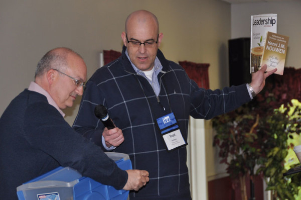 Drawings for prizes were a part of each session. Charles Milliken, pastor of the church in Franklintown, Pa., reads a name while Todd Fetters holds up the prize options.