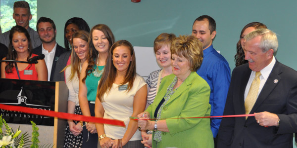 Dr. Sherilyn Emberton cuts the ribbon. (Mayor Tom Henry is on the right.)