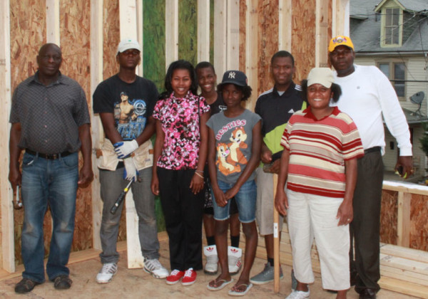 The Lascase family is busy helping finish a Habitat for Humanity home in Chambersburg, which they will be moving into. Left to right: friend of family and volunteer Eliavme Louis Charles; Lascase son Jonathan, daughter Syndy, son Davidson, daughter Sooyann, son Meatchacson, mother and wife Aurore, and Pastor of Salem Haitian Congregation-Salem United Brethren Church Gener Lascase. (Photo by Frieda Stayman - For Public Opinion)