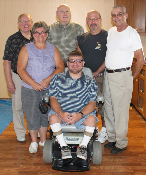 """Barbara Hilterbrand (second from left) poses with fellow members of New Hope United Brethren Church, in Huntington, who have renovated her house to enhance its wheelchair-accessibility for her son, Jeff (front center). With the Hilterbrands are (l-r in back) Rev. Ray Seilhamer, Alan Brown, Marv Beady, and Paul Buzzard. """" width=""""437"""" height=""""550"""" /> Barbara Hilterbrand (second from left) poses with fellow members of New Hope United Brethren Church, in Huntington, who have renovated her house to enhance its wheelchair-accessibility for her son, Jeff (front center). With the Hilterbrands are (l-r in back) Rev. Ray Seilhamer, Alan Brown, Marv Beady, and Paul Buzzard."""
