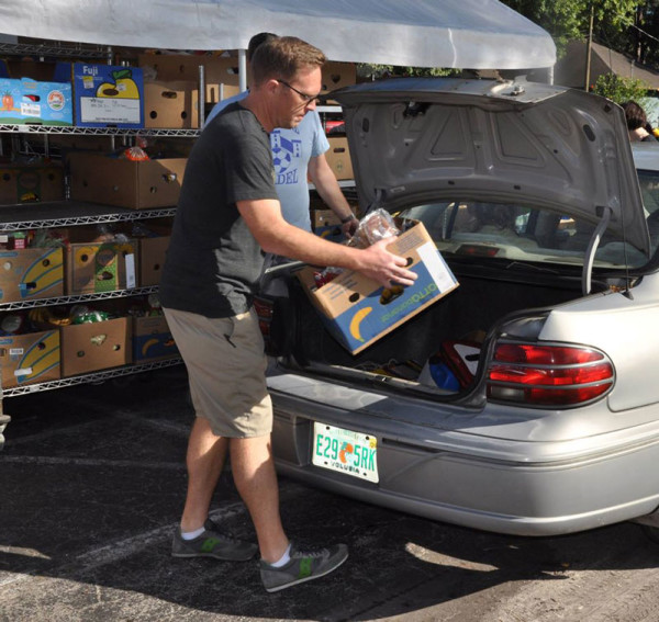 Andy Sikora, pastor of ReNew Ministries (Berea, Ohio), loading a box into a vehicle.