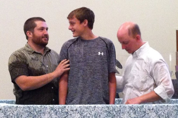 Marcus Flood (left) and Brad Kittle (right), senior pastor of Praise Point, baptizing a youth.