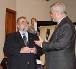 Bishop Phil Whipple (right) presenting a retirement pin to Mike Arnold.