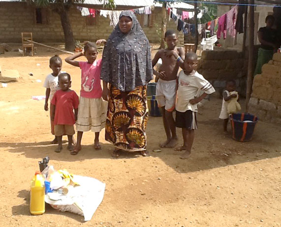 A Muslim mother and children receive relief supplies while under quarantine in the nearby village of Luawa Jong.