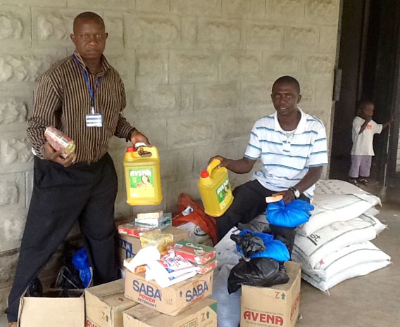 Bishop John Pessima (right) and conference administrator Justin Marva sort through supplies for quarantined families.