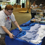 Christy Hoffman, a volunteer from Huntington, arranging new shirts bearing the UB logo.