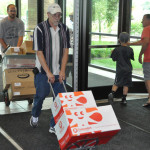 JR Reich, followed by  David Kline, bringing boxes into Reslife Church.