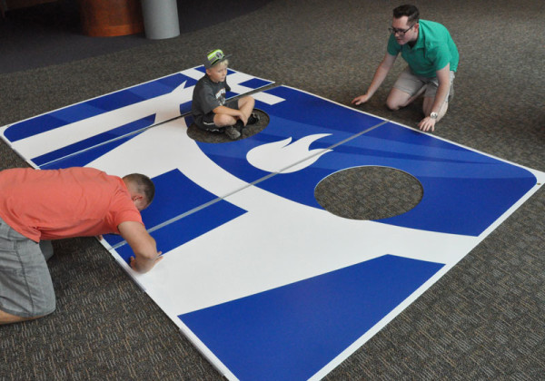Josh Good and Josh Greenfield assembling a large cutout of the UB logo.