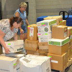 Marci Hammel and Judy Dyer unpacking boxes for the Church Resources table.