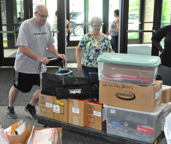Todd Fetters pushing in a cart filled with materials for the conference, as Cathy Reich watches.