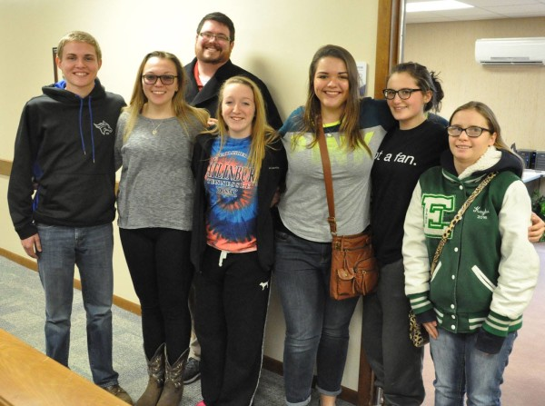 Pastor Adam Wlil (back) with seven teens interested in attending Huntington University.