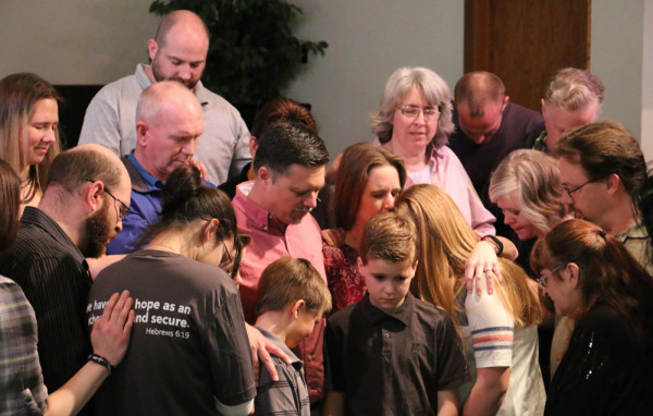 Members of the Anchor congregation gather around the Hallman family for a prayer time on Palm Sunday.