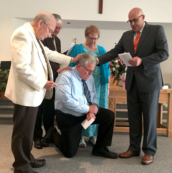 Bishop Todd Fetters (right) conducts the ordination of Eldon Grubb.
