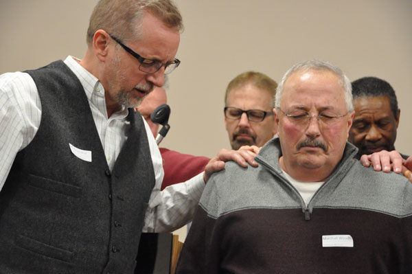 Jeff Bleijerveld praying for Marshall Woods, one of the two cluster leaders who is retiring as pastor.