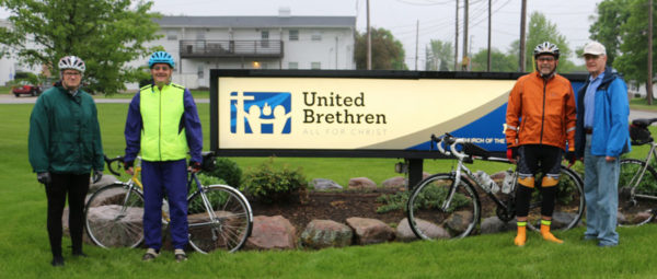 The biking team at the sign outside the UB National Office.