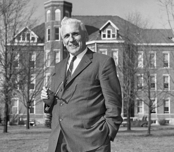 Dr. Elmer Becker in front of the Huntington University Administration Building.