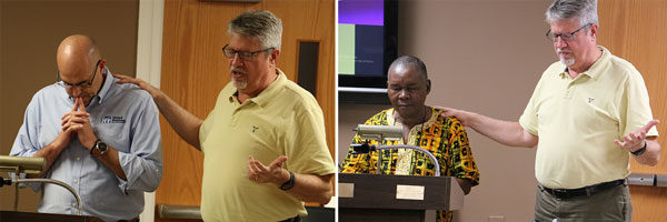 After each report, Brian Magnus stood with the delegate as prayer was offered for that country. Left: with Bishop Todd Fetters of the United States. Right: with Moses Somah of Liberia.